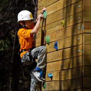 A scout climbs a rock wall course